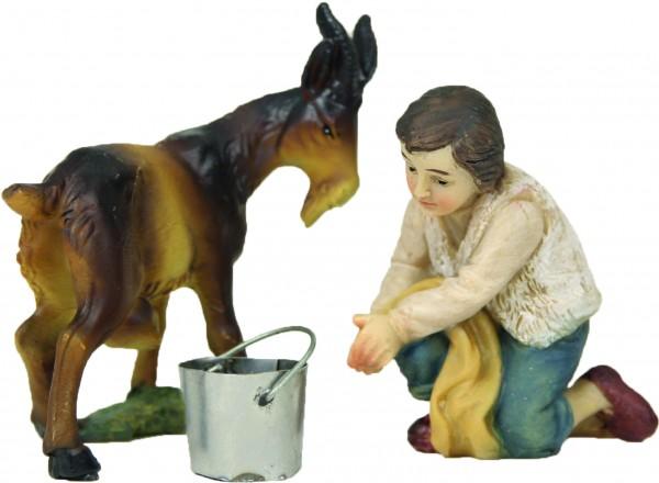 Junge mit Ziege beim Melken
